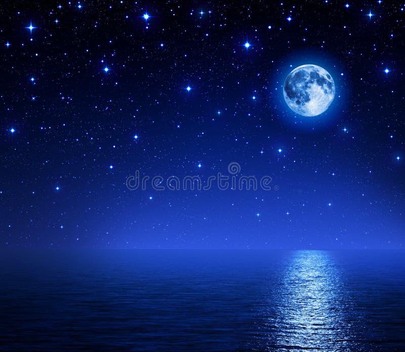 Супер луна в звёздном небе на море стоковые фото