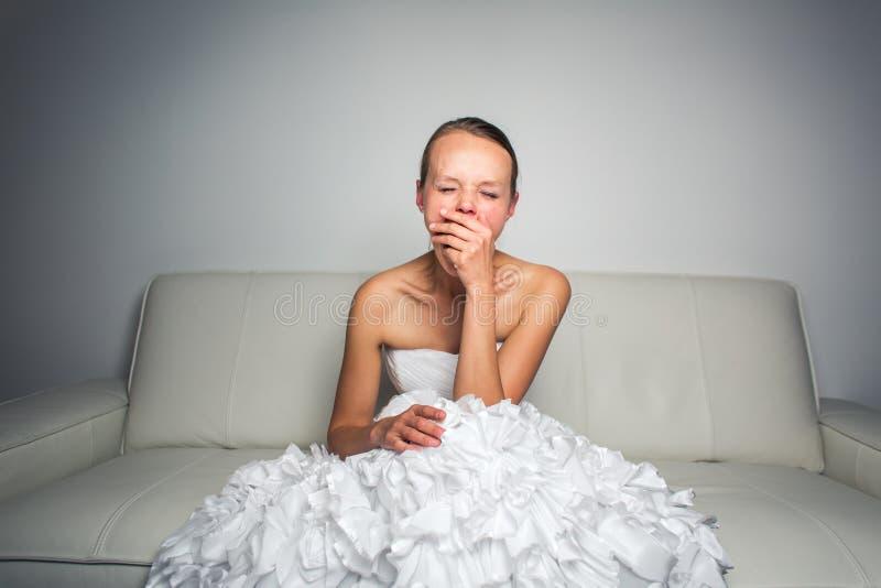 Супер утомленная шикарная невеста сидя на софе стоковое фото rf