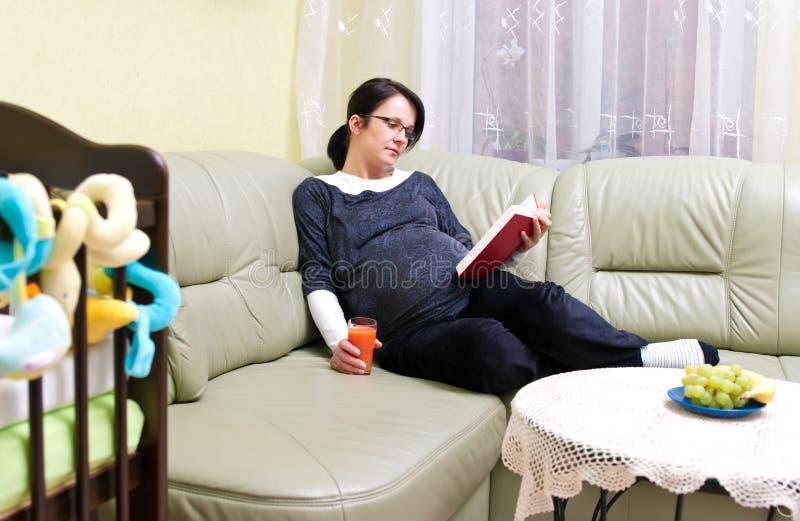 супоросая женщина чтения стоковая фотография rf