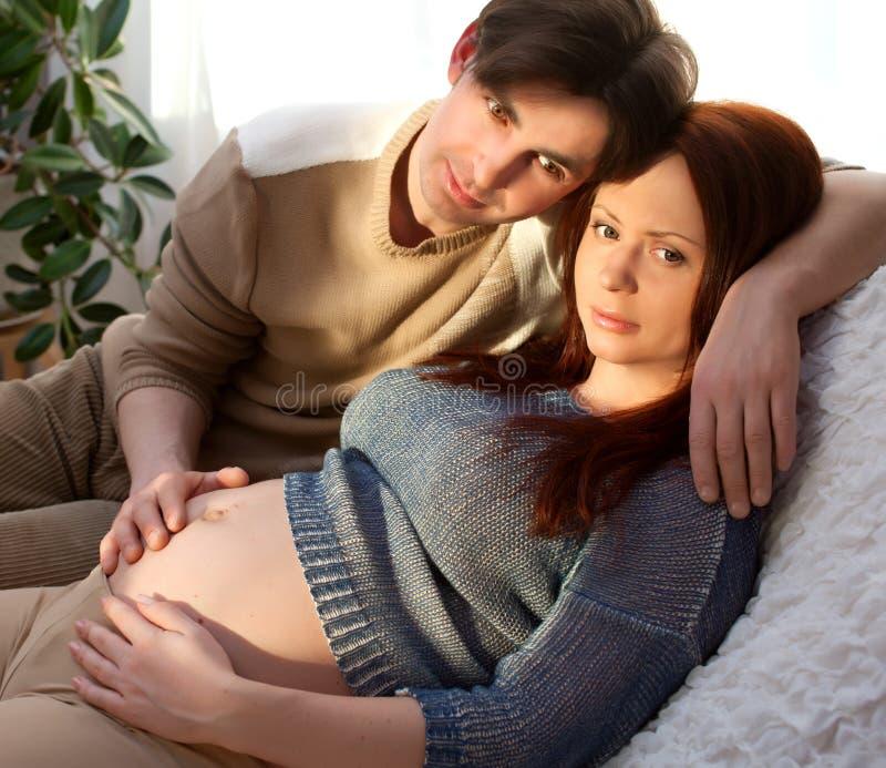 Супоросые пары ослабляя на софе, мечтая. Нежность стоковые фото