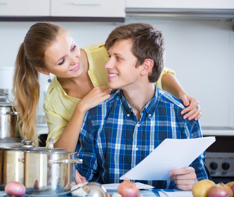 Супруги подписывая документы и усмехаясь на кухне стоковые фото