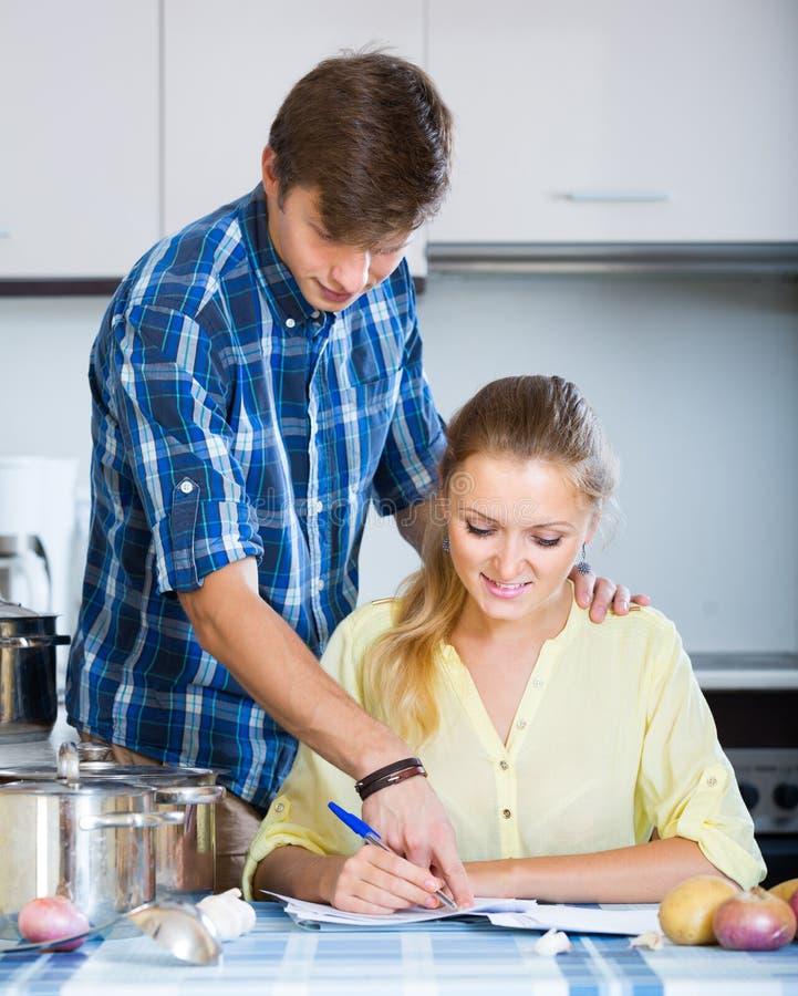 Супруги подписывая документы и усмехаясь на кухне стоковая фотография rf