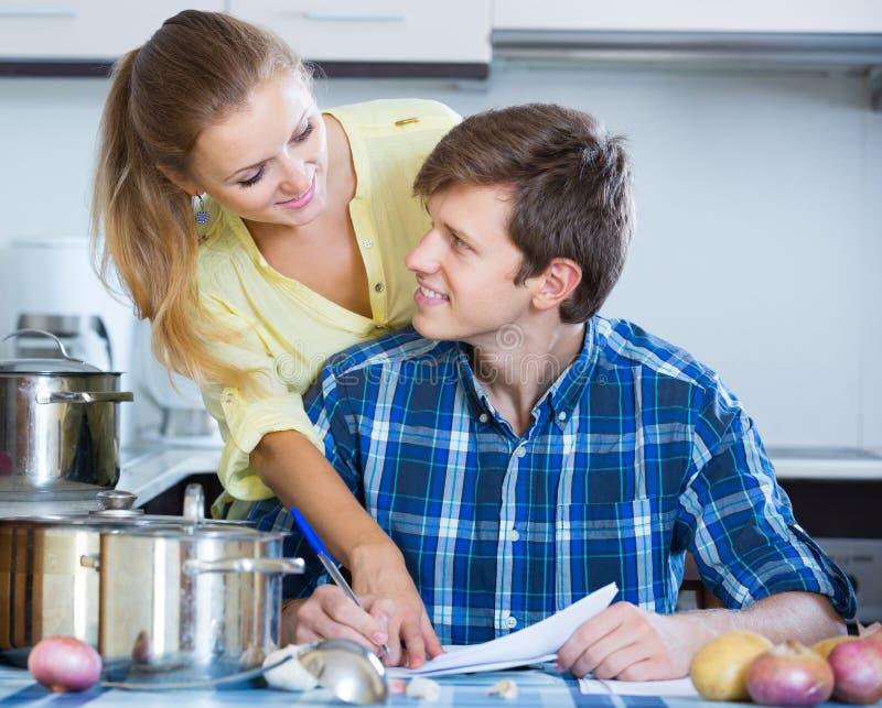 Супруги подписывая документы и усмехаясь на кухне стоковое изображение rf
