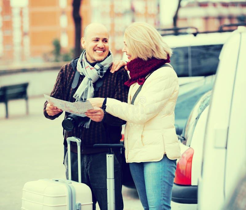 Супруги с багажем и картой стоковое фото rf