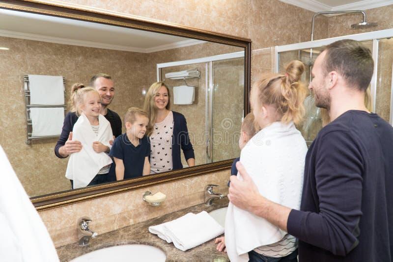 Супруг, жена и дети стоят перед зеркалом в ванной комнате гостиничного номера и усмехаются Молодая семья стоковая фотография rf