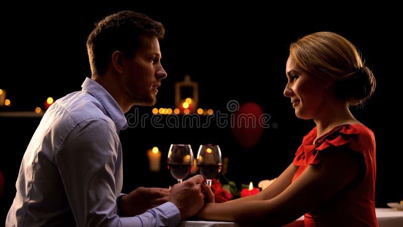 Супруг и жена держа руки и восхищая один другого на романтичном обедающем стоковые изображения