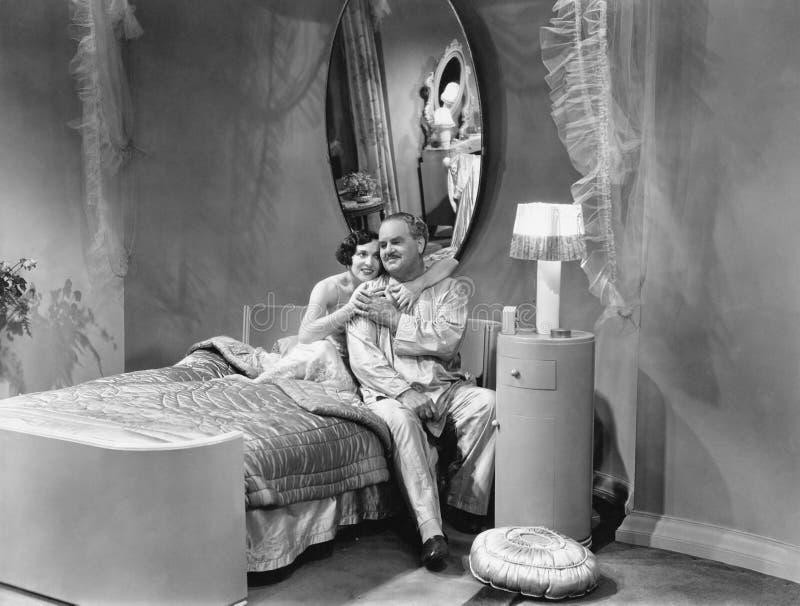 Супруг и жена обнимая на кровати (все показанные люди более длинные живущие и никакое имущество не существует Гарантии поставщика стоковые фотографии rf