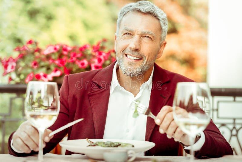 Супруг нося стильную куртку имея обедающий снаружи стоковая фотография