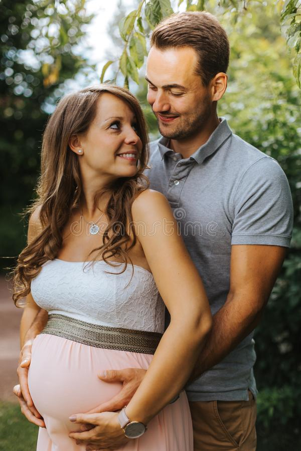 Супруг обнимает его красивую беременную жену от позади стоковые фотографии rf