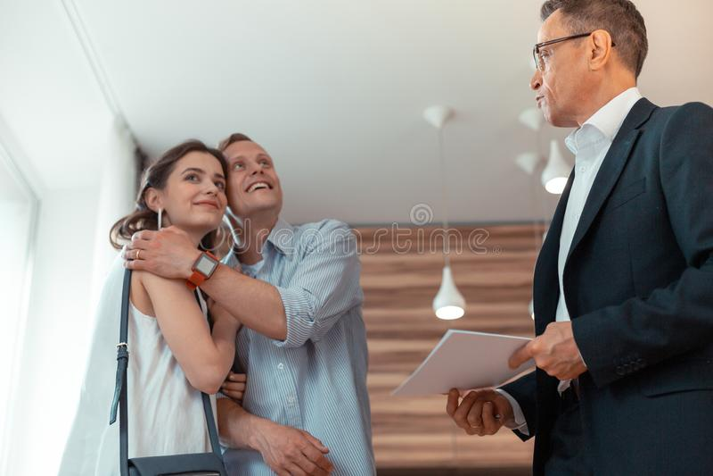 Супруг обнимая жену после покупая положения дома около риэлтора стоковое фото rf