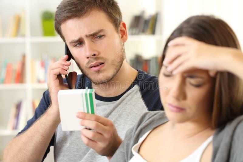 Супруг помогая его больной жене вызывая доктора стоковое изображение rf