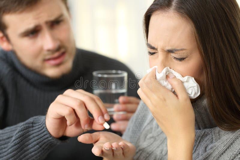 Супруг помогая его больной жене давая медицины стоковая фотография rf