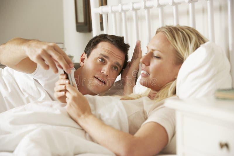 Супруг Complaing как жена использует мобильный телефон в кровати стоковые фотографии rf