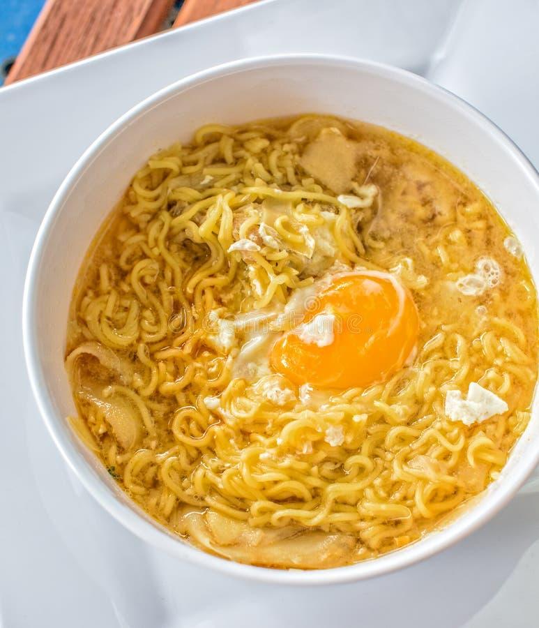 Суп лапши с яичком на белой плите стоковое изображение