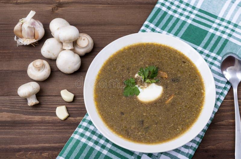 Суп гриба со сметаной и травами, грибами, полотенцем в зеленой клетке, ложкой, деревянной коричневой таблицей стоковые фото