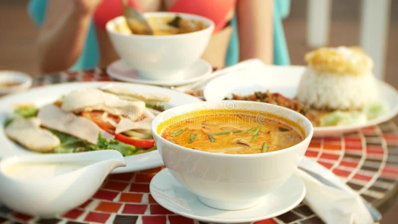 Суп креветки пряный тайское блюдо с кислым и пряным вкусом busty девушка в бикини ест Том Ям на таблице бассейном стоковые фотографии rf