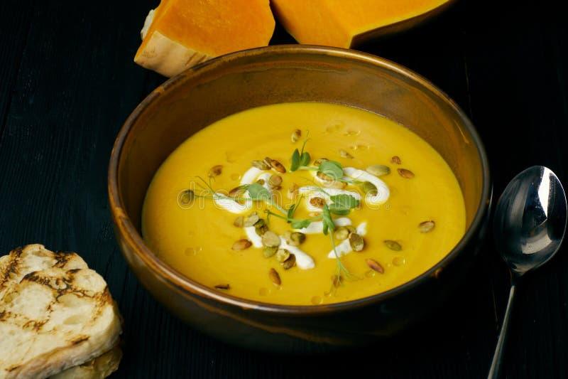 Суп тыквы в шаре со сливками и семенах тыквы Суп Vegan деревянное предпосылки темное стоковое изображение rf