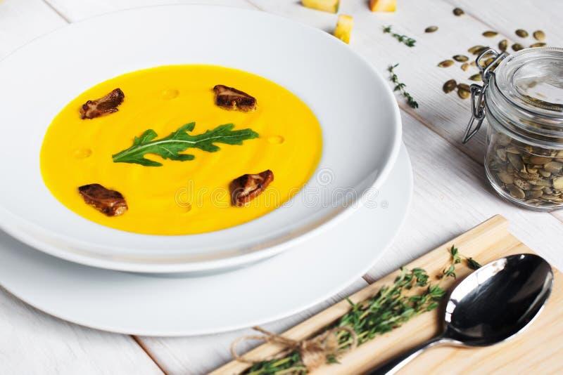 Суп тыквы с семенами и ложкой на таблице стоковые изображения