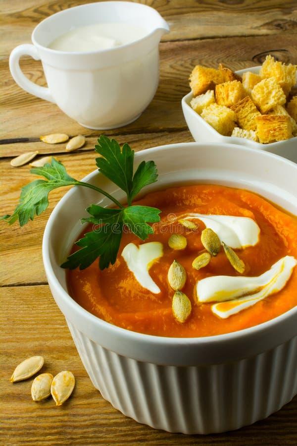 Суп тыквы с сливк на темной деревянной предпосылке стоковая фотография rf