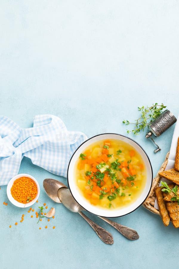 Суп чечевицы с овощами и свежей петрушкой на плите на таблице стоковое фото