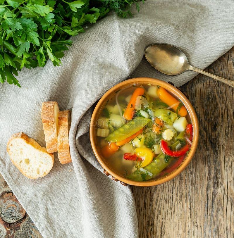 Суп яркого весеннего овоща диетический вегетарианский Взгляд сверху, предпосылка коричневого цвета деревенская деревянная, linen  стоковое изображение