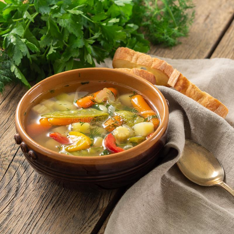 Суп яркого весеннего овоща диетический вегетарианский Взгляд со стороны, предпосылка коричневого цвета деревенская деревянная, li стоковые изображения