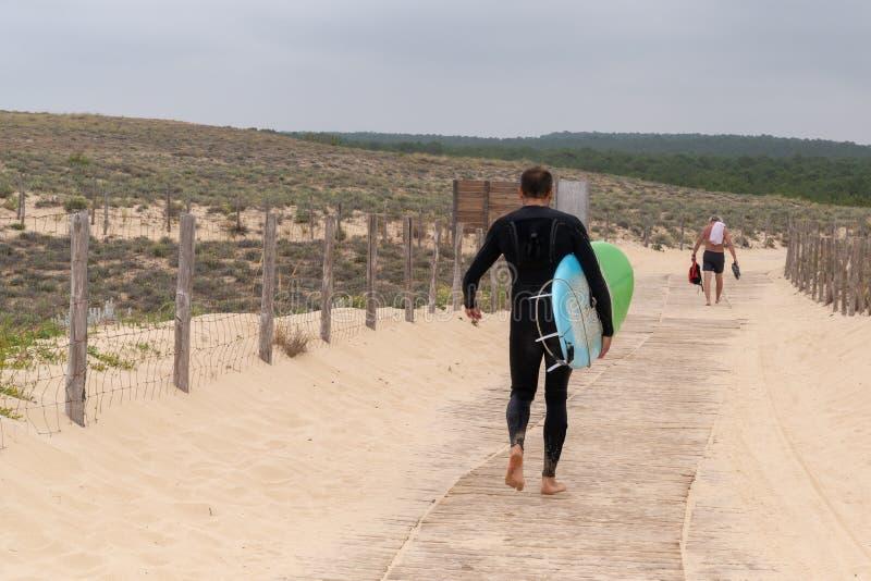 Сурфер, несущий доску, идущий в море в черных водолазных костюмах, отпрРстоковая фотография rf