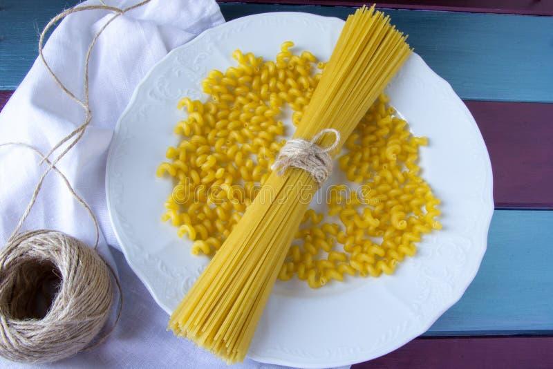Сухие спагетти и суетливо макаронные изделия на белой плите стоковое изображение