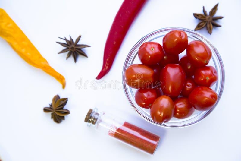 Сухие специи и травы в стеклянном опарнике с пробочкой, шаре томатов вишни и перцах chili, белой предпосылке стоковые фотографии rf