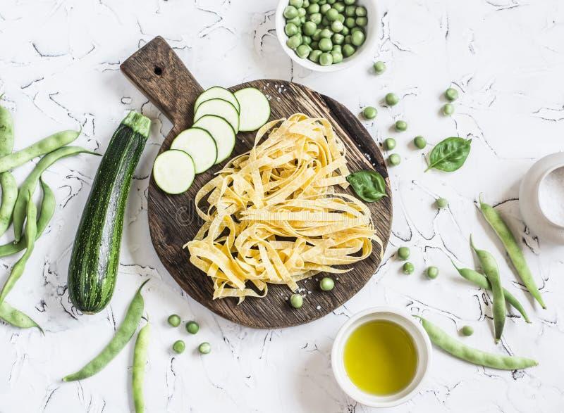 Сухое tagliatelle макаронных изделий, цукини, зеленые фасоли и горохи, оливковое масло на светлой предпосылке стоковая фотография rf