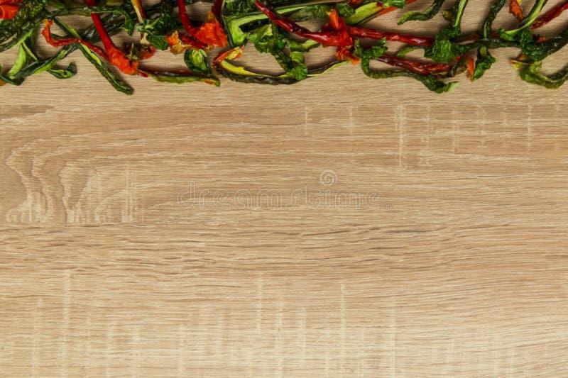 Сухой красный и зеленый болгарский перец на деревянной предпосылке Космос для текста стоковая фотография