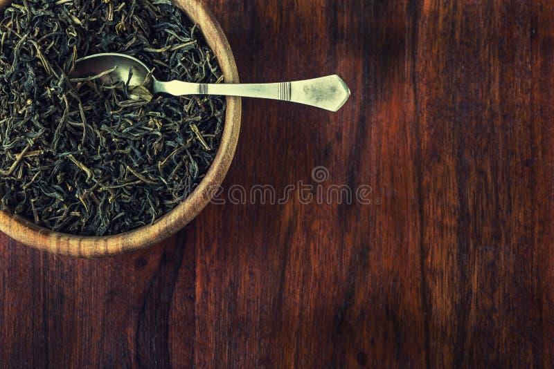 Сухой чай в деревянной плите на деревянном столе стоковое изображение