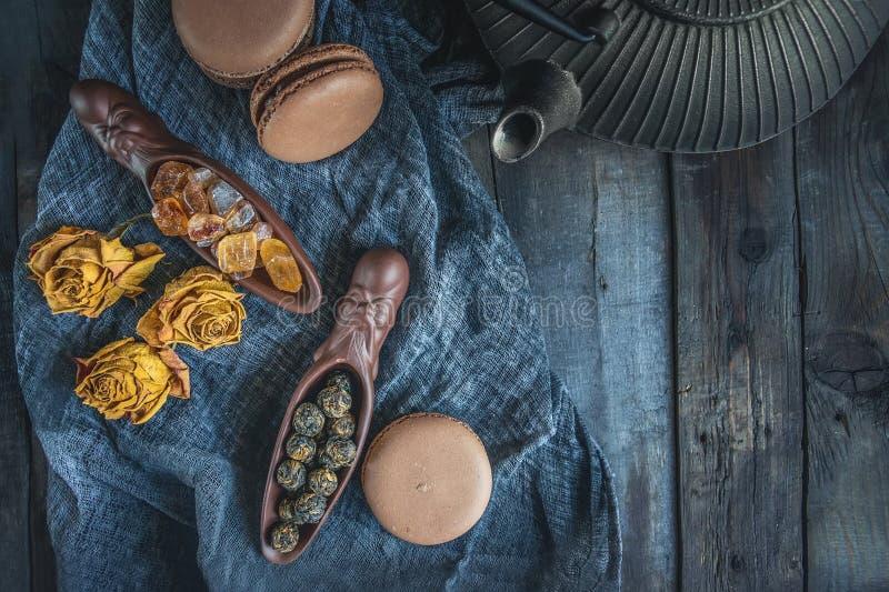 Сухой черный чай Свернутые листья в большом жемчуге Керамический figural лопаткоулавливатель с славным плоским чайником чугуна ки стоковые фотографии rf