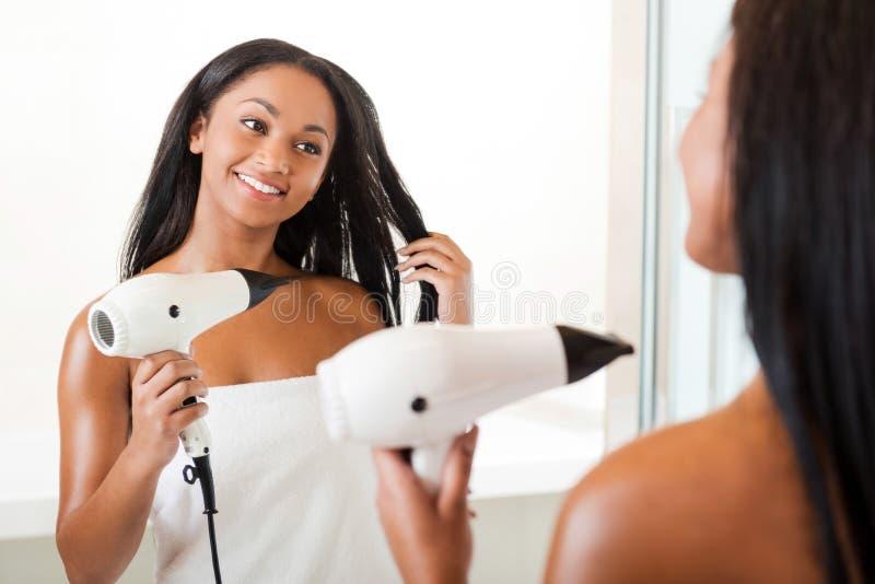 Суша волосы в ванной комнате стоковые фотографии rf