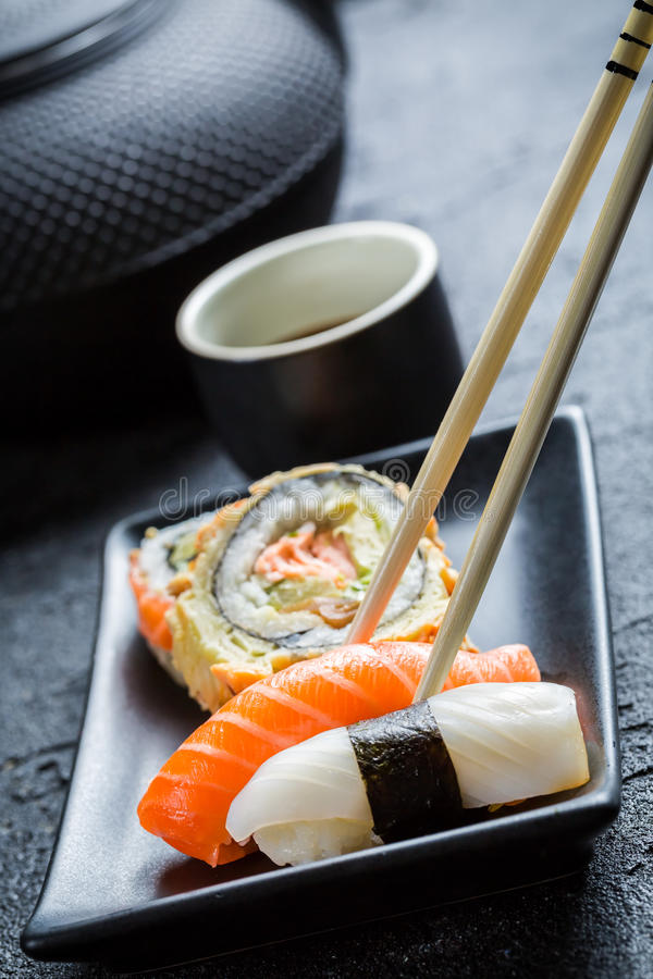Download Суши в черное керамическом съеденные с палочками Стоковое Фото - изображение насчитывающей культура, calamari: 40586128
