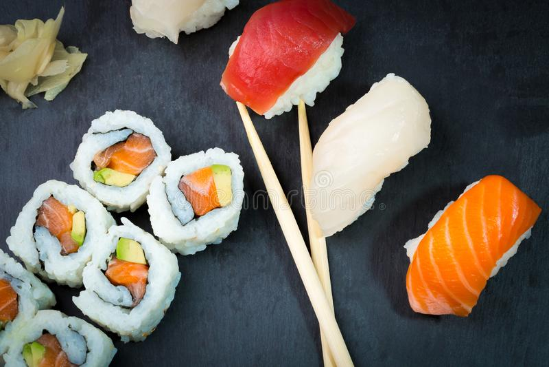 Суши и сасими свертывают на черном каменном slatter Свежая сделанная суши установить с семгами, креветками, wasabi и имбирем Трад стоковые изображения rf