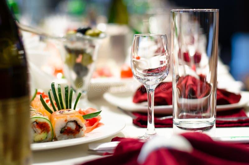Суши и стекла на официально обеденном столе стоковая фотография