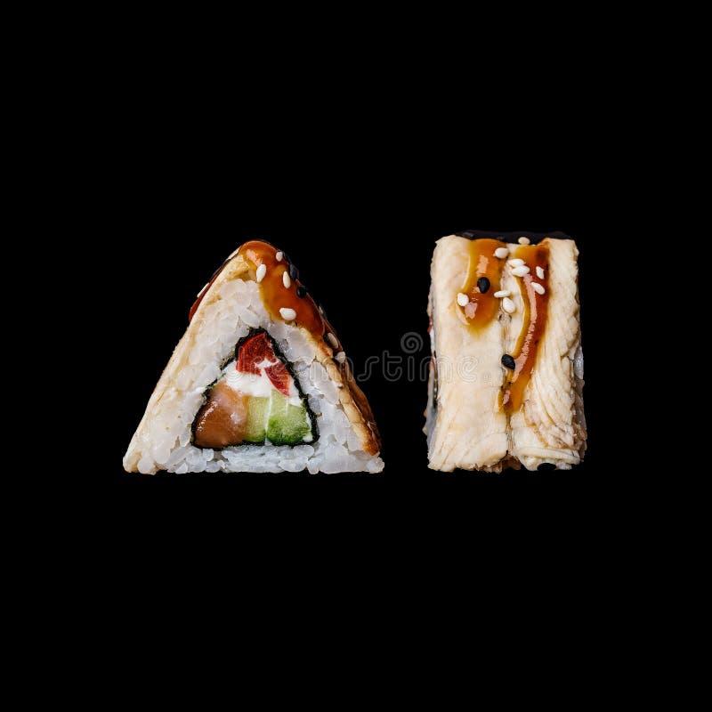 Суши Крен Katana с семгами, огурцом, томатом вишни, плавленым сыром и копченым угрем, изолированными в черной предпосылке стоковые изображения rf