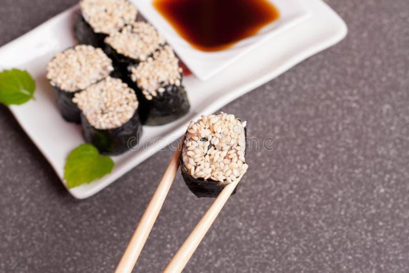 Суши с сезамом на белой плите стоковые изображения