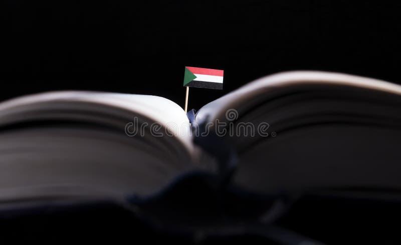 Суданский флаг в середине книги Знание и образование стоковые фотографии rf