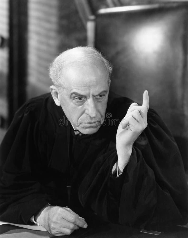 Судья в зале судебных заседаний указывая его палец вверх (все показанные люди более длинные живущие и никакое имущество не сущест стоковые фото