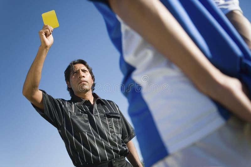 Судья-рефери показывая желтую карточку стоковое изображение rf