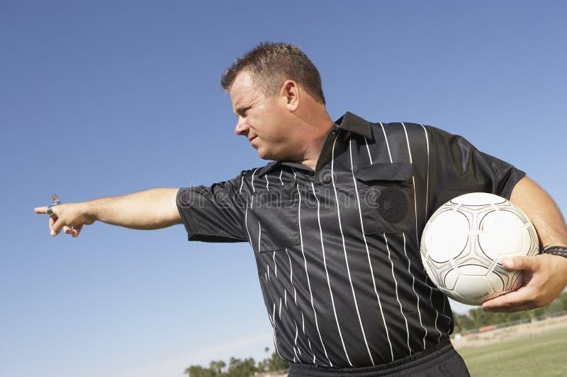 Судья-рефери с указывать шарика футбола стоковое фото rf