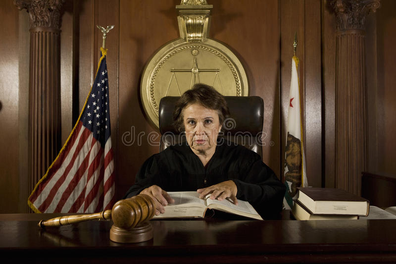 Судья сидя в зале судебных заседаний стоковое фото