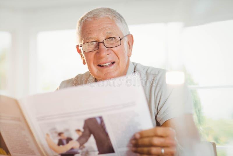 Сфокусированная газета чтения старшего человека стоковое фото