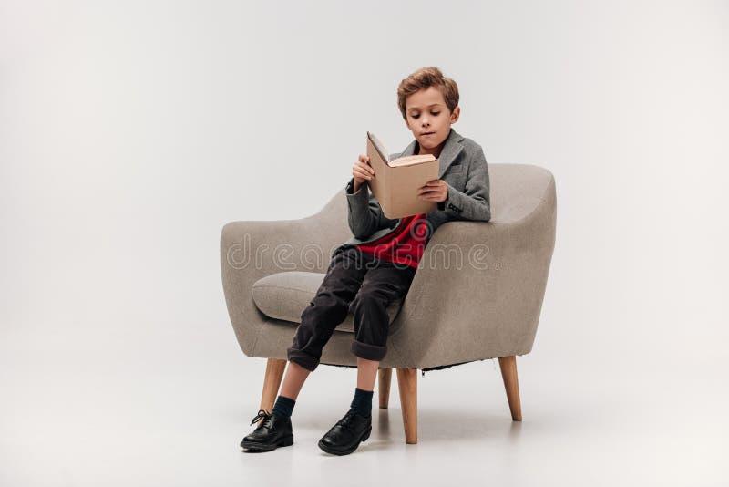 сфокусированная маленькая книга чтения школьника стоковое фото rf