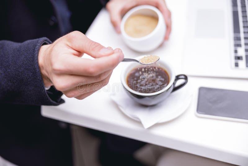 Сфокусированная фотография на мужской руке, которая держит чайную ложку стоковая фотография