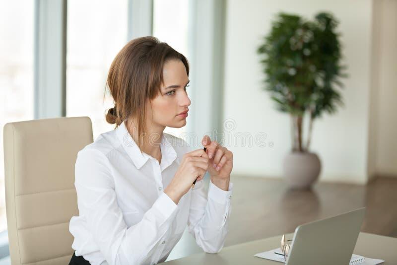 Сфокусированное женское усаживание на столе планируя или принимая во внимание новое proje стоковая фотография rf