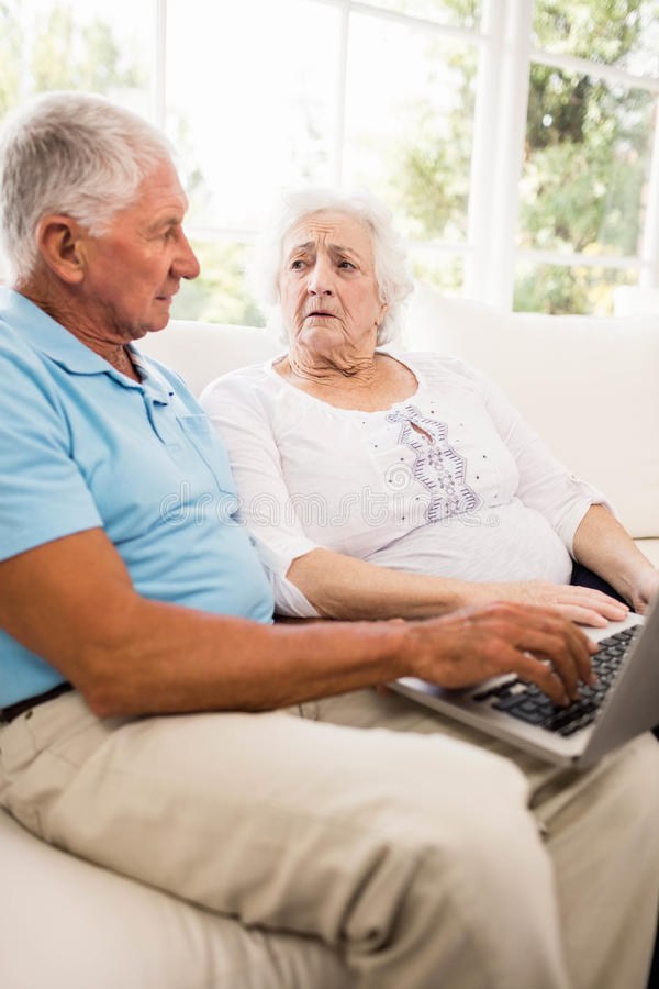 Сфокусированные старшие пары используя компьтер-книжку стоковое изображение rf