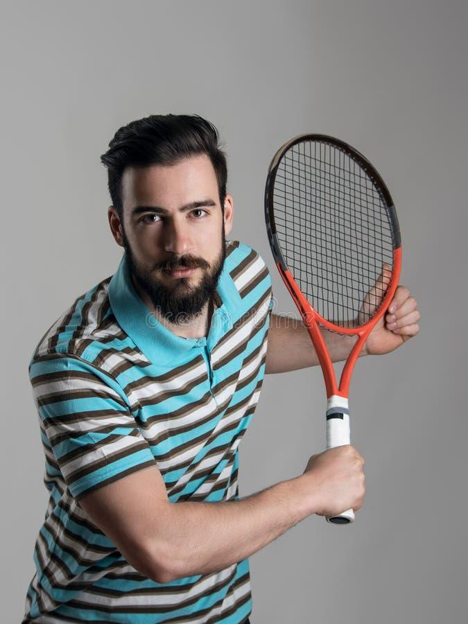 Сфокусированный бородатый загиб теннисиста держа ракетку стоковое фото